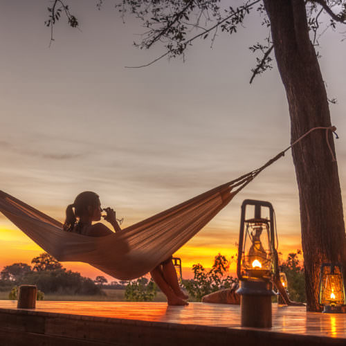 In The Saddle. Riding Safari at Macatoo, Okavango Delta, Botswana. Hammock and wine at sunset.