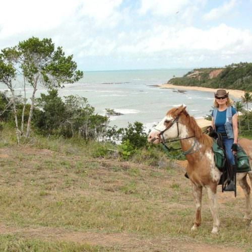 Riding Holidays in Brazil. Beach riding in Bahia. Horse and rider overlooking coastline.