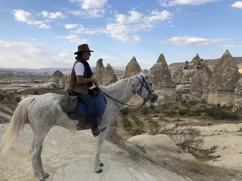 guide erchian on his horse overlooking the fairy chimneys
